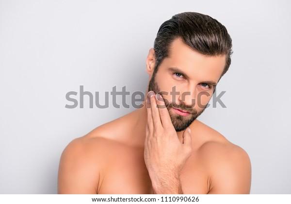 Attraktiver, brutaler, moderner, männlicher, böser, selbstbewusster, traumatischer, nackter Mann, der sein perfektes, ideales Gesicht berührt, Hand auf Bart, Wange hält, Kamera einzeln auf grauem Hintergrund ansieht