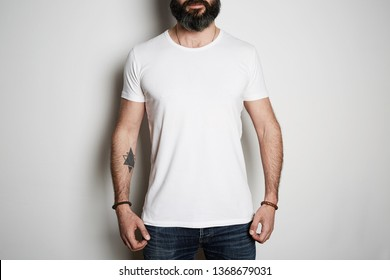 Attractive brutal tattooed bearded guy poses in blue jeans and blank gray t-shirt premium summer cotton, on white background mockup.