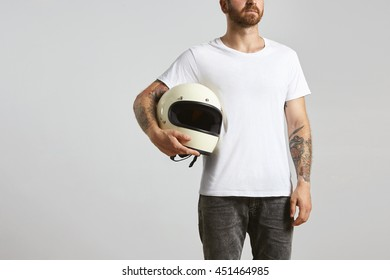 Attractive brutal tattooed bearded guy poses in black jeans and blank white t-shirt from premium thin summer cotton, holding motorbike helmet in hand, isolated on white mockup
