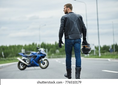 Attractive brutal unshaven young biker man wearing leather jacket boots and gloves sitting outdoors, going to his motorcycle and looking to the right side with serious confident expression on his face