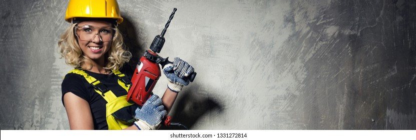 Attractive builder woman wearing protective helmet and coverall smile look at camera holding a drill in her hands pose over obsolete horizontal grey copy space wall, repair, renovation concept