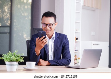 attractive business asian man working with computer laptop on wooden table at home. analyzing online data to success business