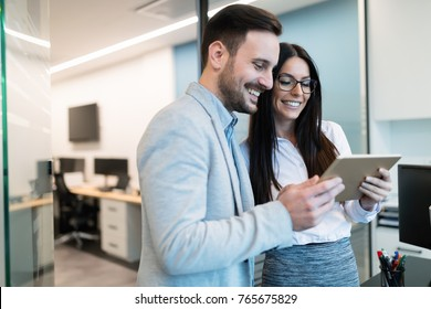 Attractive business couple using tablet in modern office