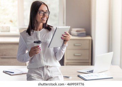 Attractive business lady in stylish clothes and eyeglasses is using a digital tablet, holding a cup of coffee and smiling while sitting on her working table in office