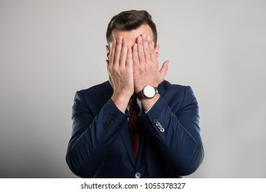 Attractive business man covering eyes like blind gesture on gray background