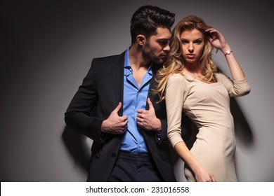 Attractive business man fixing his jacket while looking at his lover. The beautiful blonde woman is fixing her hair while looking at the camera.
