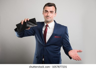 Attractive business man holding wallet upside down and gesturing on gray background