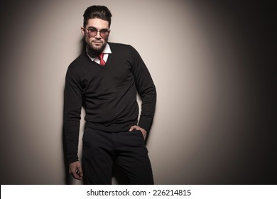 Attractive business man leaning on a grey wall with one hand in his pocket.