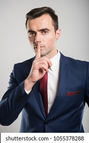 Attractive business man making sush gesture with finger on gray background