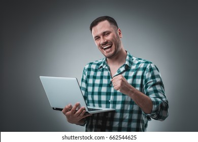 Attractive business man model in green shirt isolated on gray working with laptop, showing something by left hand.