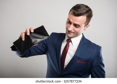 Attractive business man showing his empty wallet on gray background