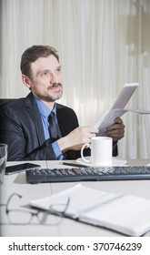 attractive business man is sitting on his desktop and smiles