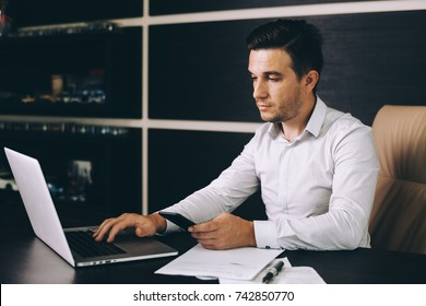 Attractive business man in smart casual wear sitting at his working place in office
