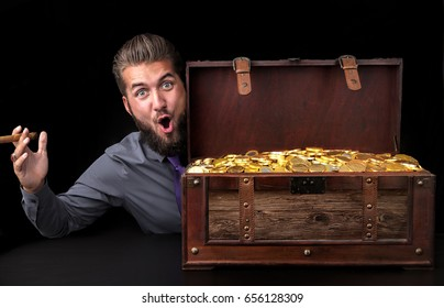 Attractive business man with a treasure chest full of gold