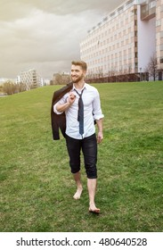Attractive business man is walking barefoot in a city park