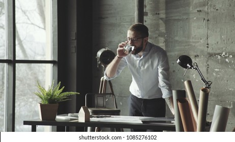 Attractive business man working on an architectural project in office takes off his glasses and rubs the bridge of his nose, feeling tired. Business man in glasses, working with drawings, feels tired.