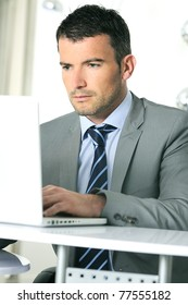 An attractive business man is working on computer