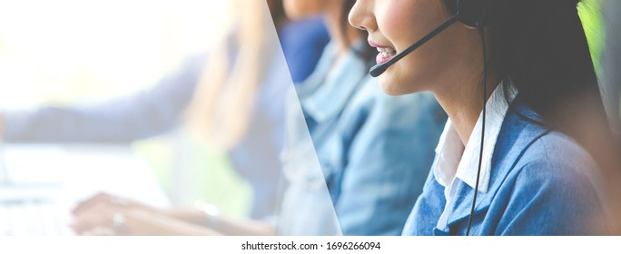 Attractive business woman Asian in suits and headsets are smiling while working with computer at office. Customer service assistant working in office. panorama and panoramic banner design