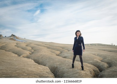 Attractive business woman in blue dress standing tall in dry abandoned landscape with blue sky