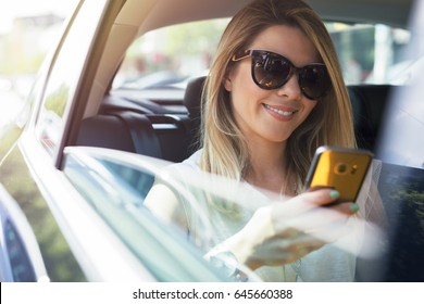 Attractive business woman in car. Writing a message on her mobile phone.