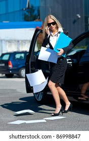 attractive business woman dropping papers near to her car in parking lot