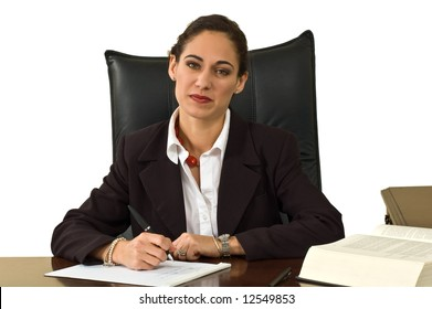 Attractive business woman at her desk, pondering the work she is doing.