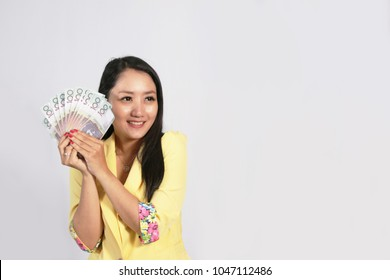 Attractive business woman holding a cash australian dollar in her hand which she has won in an unexpected windfall. Attractive young woman holding australian dollar banknotes and smiling isolated