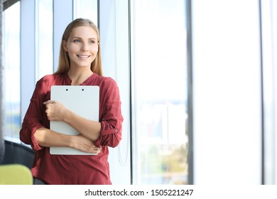Attractive business woman looking at camera and smiling while standing in the office near the window