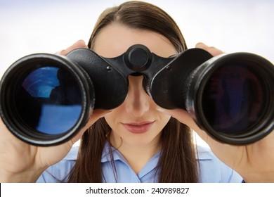 attractive business woman looking through binoculars