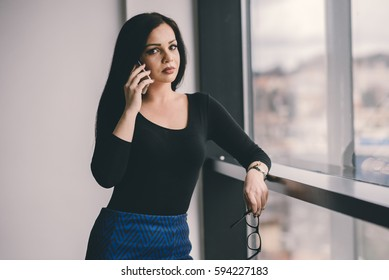 Attractive business woman looks at photographer while holding cellphone next to ear