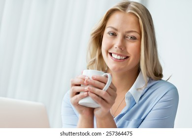 Attractive business woman with a mug in office