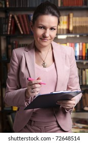 Attractive business woman in pink suit holding clipboard and pink  highlighter in library