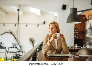Attractive business woman sitting at her desk and drinking coffee.