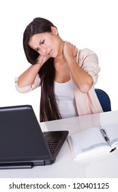 Attractive business woman with a stiff neck from sitting working on her laptop grimacing in pain