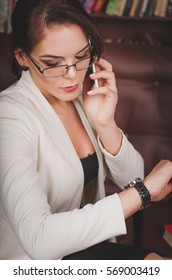 attractive business woman in a business suit with glasses sitting on a leather brown sofa in the office to view, talking on the phone and looks at the clock on her arm. Business communication concept