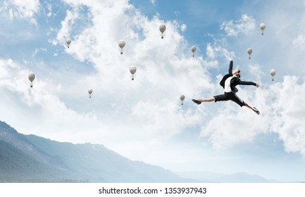 Attractive business woman in suit jumping in the air as symbol of active life position. Skyscape with flying balloons and nature view on background. 3D rendering.