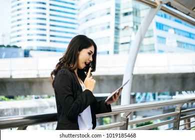 Attractive business woman using a digital tablet while standing in front of office building.