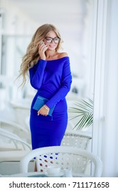 Attractive business woman wearing glasses and a blue dress talking on the phone