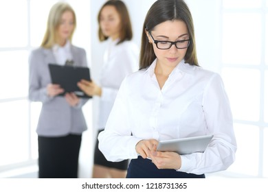 Attractive business woman working with a tablet pc against the background of colleagues. Lawyer or secretary specialist at work