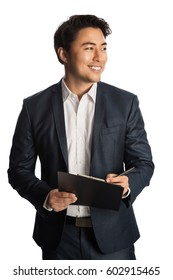 Attractive businessman in a blue suit and white shirt, holding a clipboard and a pen. Standing against a white background with a big toothy smile.