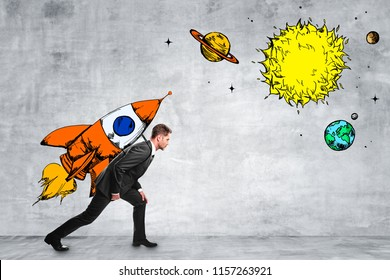 Attractive businessman carrying creative rocket sketch on concrete wall background. Startup and entrepreneurship concept