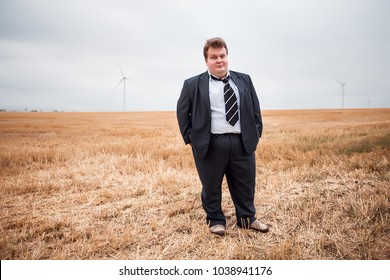 Attractive businessman in a classic suit having fun, funny guy smiles, tie, concept, man in the field, fat man, happy man, good fat man