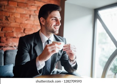 Attractive businessman drinks coffee and looks into the window. Happy young man in suit with cup
