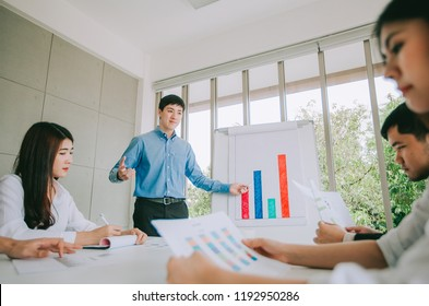 Attractive businessman giving a presentation to his employees in the meeting room. Businesspeople working on laptop and document in foreground.