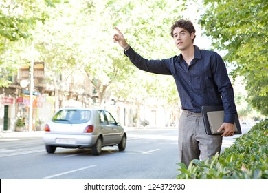 Attractive businessman hitching a taxi in a tree aligned street in the city, holding paperwork and folders.
