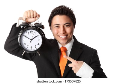 Attractive businessman holding a clock, wearing a suit and orange tie. White background.