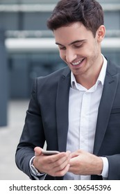 Attractive businessman is holding a mobile phone and messaging to his colleague. He is looking at the technology with joy and smiling. The worker is standing near his office