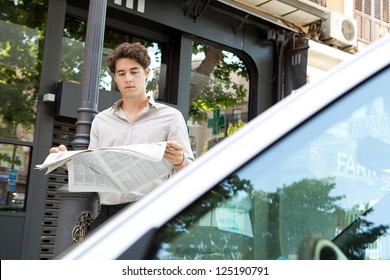 Attractive businessman leaning on a lamp post in the city behind a car, reading the newspaper.