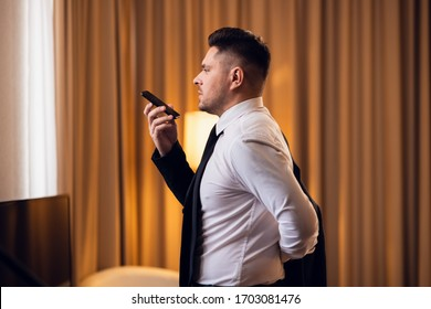 An attractive businessman making phone calls, while dressing in his hotel room. A busy morning in a luxurious hotel