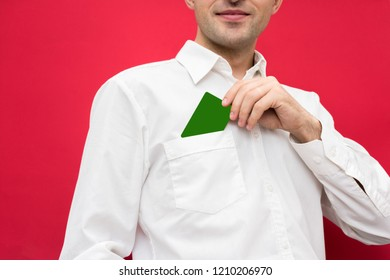 Attractive businessman, man who takes out blank business card from the pocket of his shirt to the camera, red background with copy space, for advertisement, front view, close up